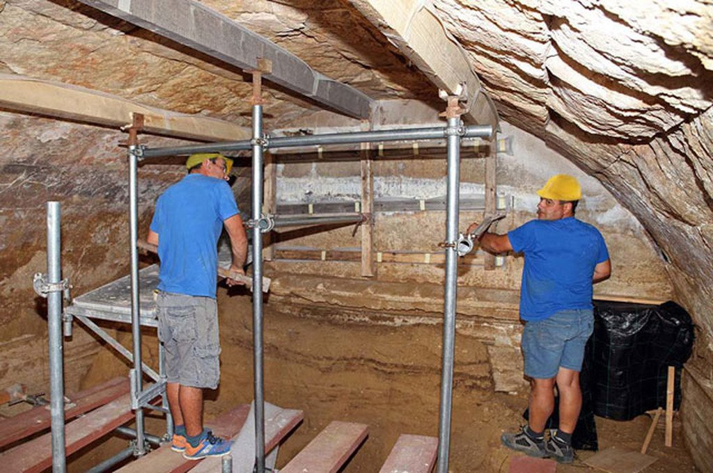 Archaeologists work inside the tholos, a type of Greek subterranean domed tomb chamber shaped like a beehive