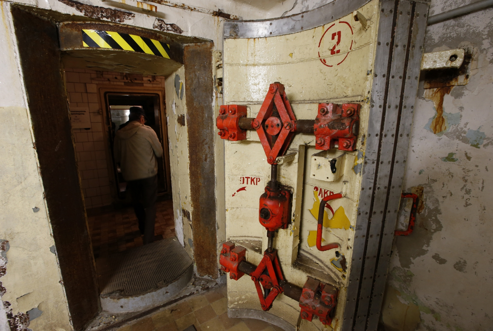 A guide walks next to a heavily fortified door to a bunker used after 1945 till 1994 by the Soviet army as the so-called