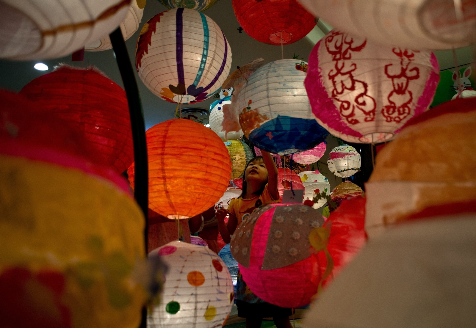 A child plays amongst multi-coloured paper lanterns put up to celebrate Mid-Autumn Festival in Malaysia