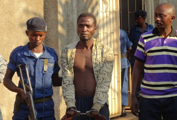 A Burundian policeman escorts suspect Christian Claude Butoyi (C) after he was arrested in Bujumbura for the murder of three Italian nun