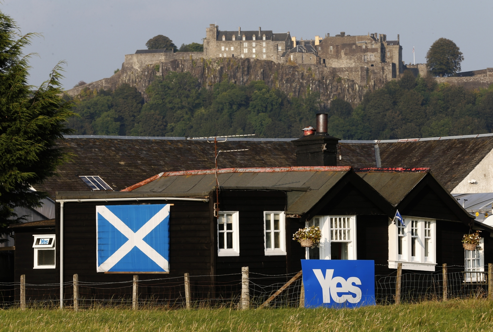 "A house displaying a saltire and ""yes"" banner is seen in front of Stirling Castle, Scotland September 10, 2014."