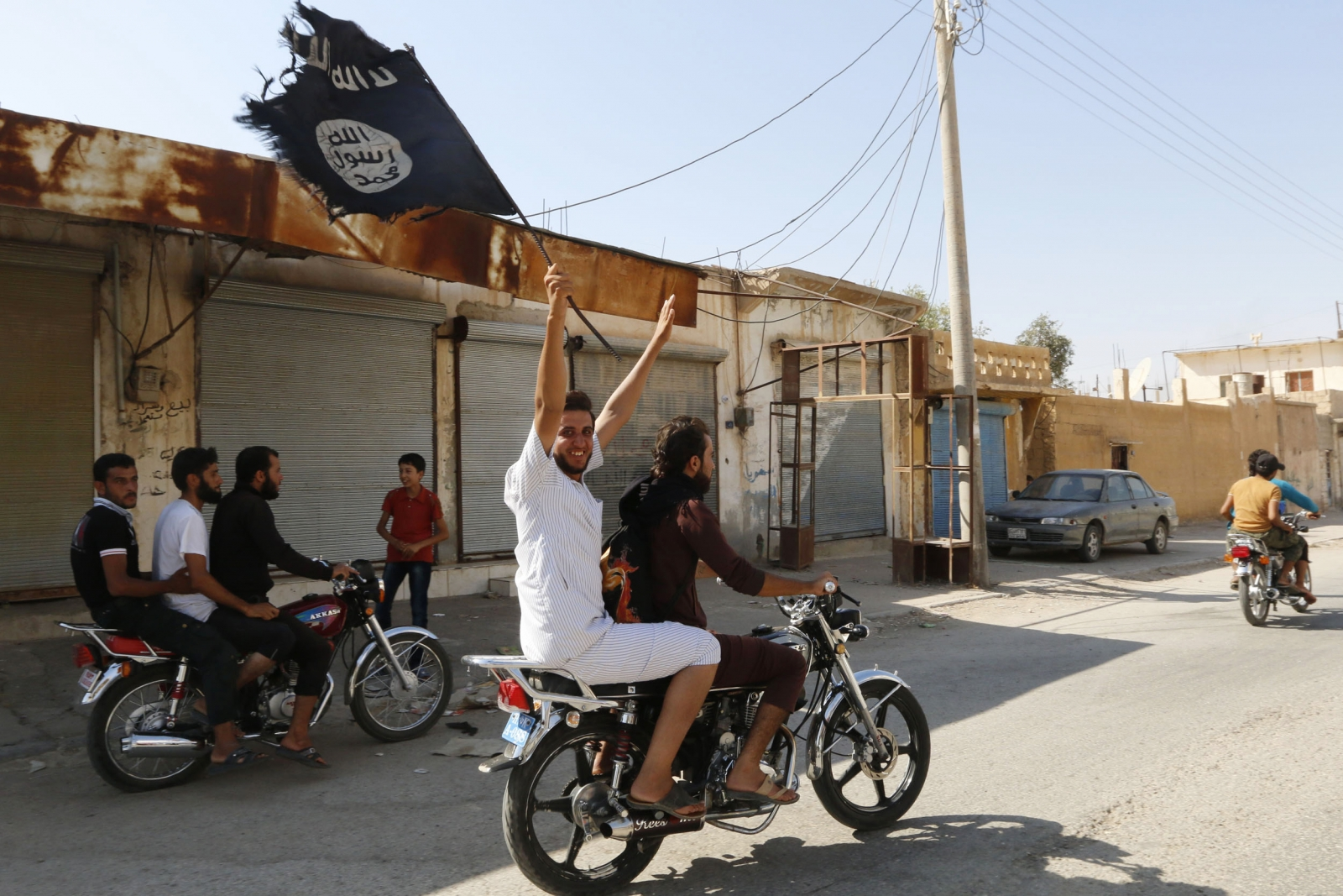 A resident of Tabqa city touring the streets on a motorcycle waves an Islamist flag in celebration after Islamic State militants took over Tabqa air base
