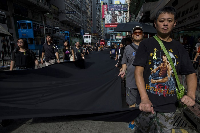 Pro-democracy activists march through the streets of Hong Kong carrying a 500-metre long black cloth.