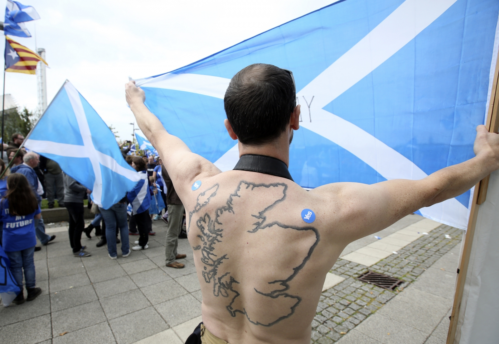 A 'Yes' supporter with a tattoo of Scotland on his back holds a Saltire flag at a rally outside the BBC in Glasgow, Scotland September 14, 2014.
