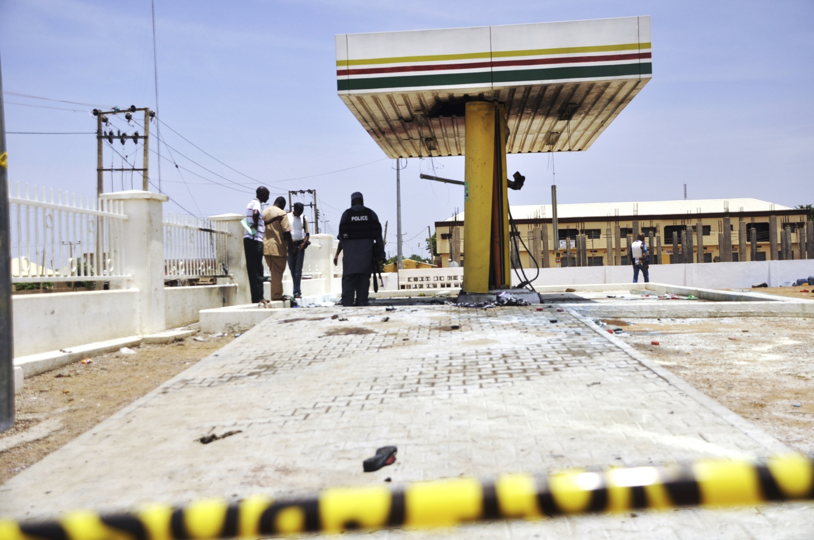 Members of the bomb squad inspect a Nigerian National Petrolium Corporation (NNPC) petrol station after a female suicide bomber blew herself in the city of Kano July 28