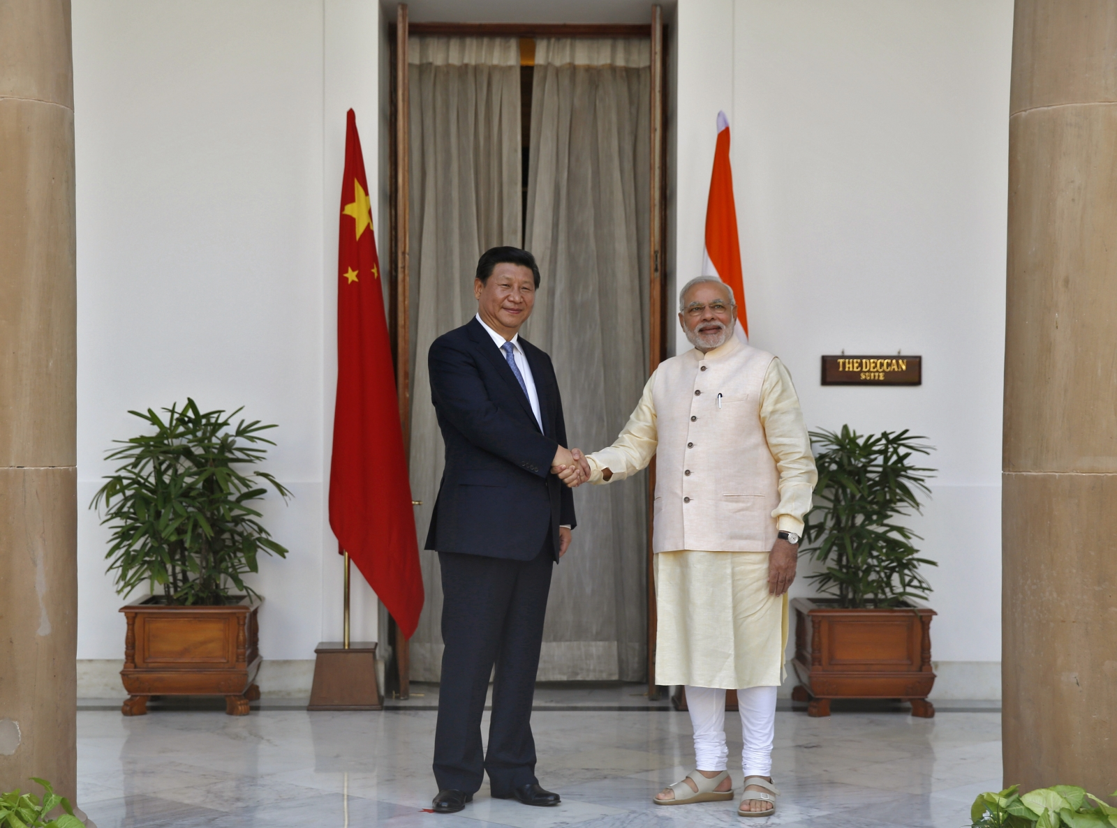 India's Prime Minister Narendra Modi (R) and China's President Xi Jinping shake hands during a photo opportunity ahead of their meeting at Hyderabad House in New Delhi
