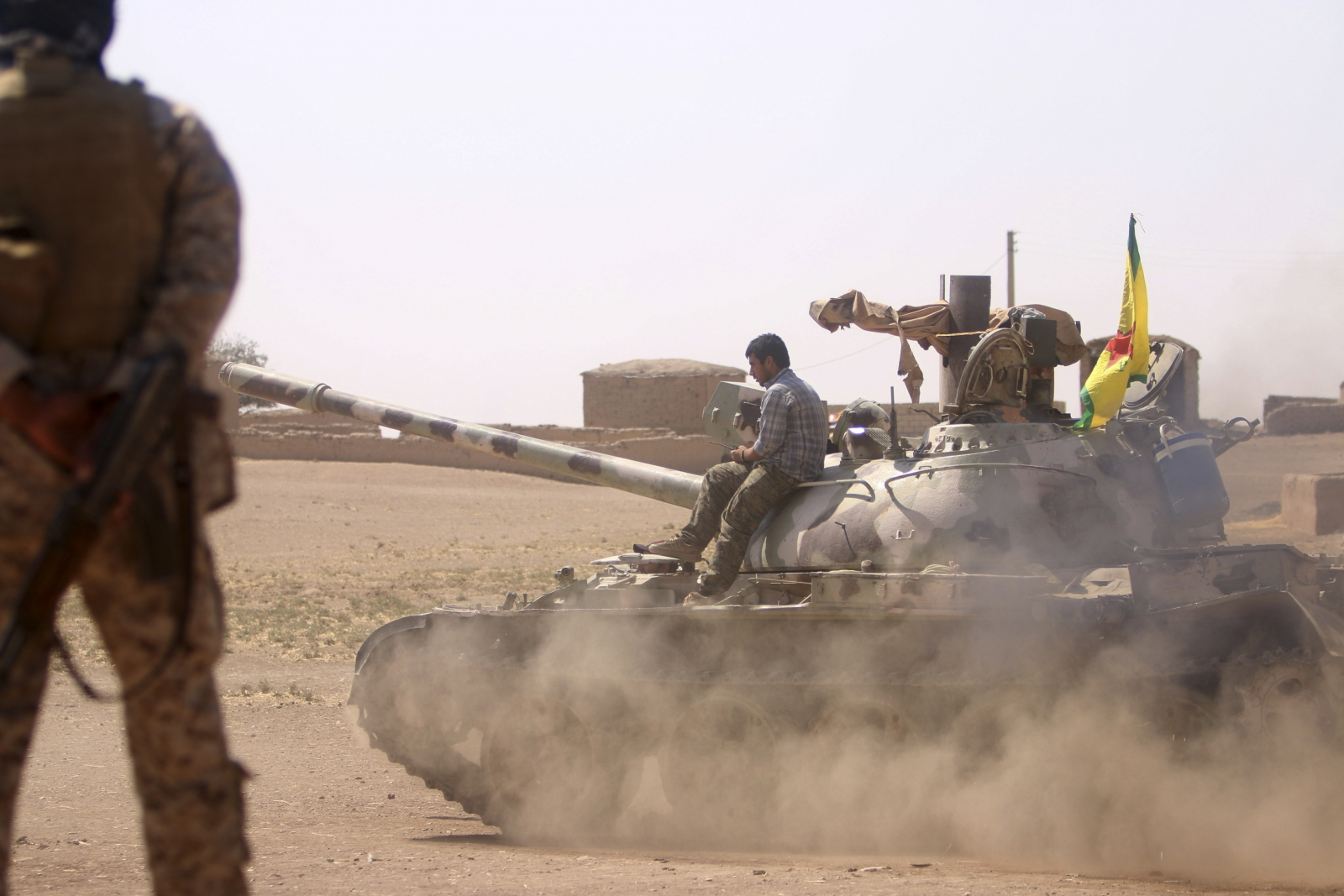 Kurdish People's Protection Units (YPG) drive a tank in villages surrounding Jazaa, in Qamishli countryside