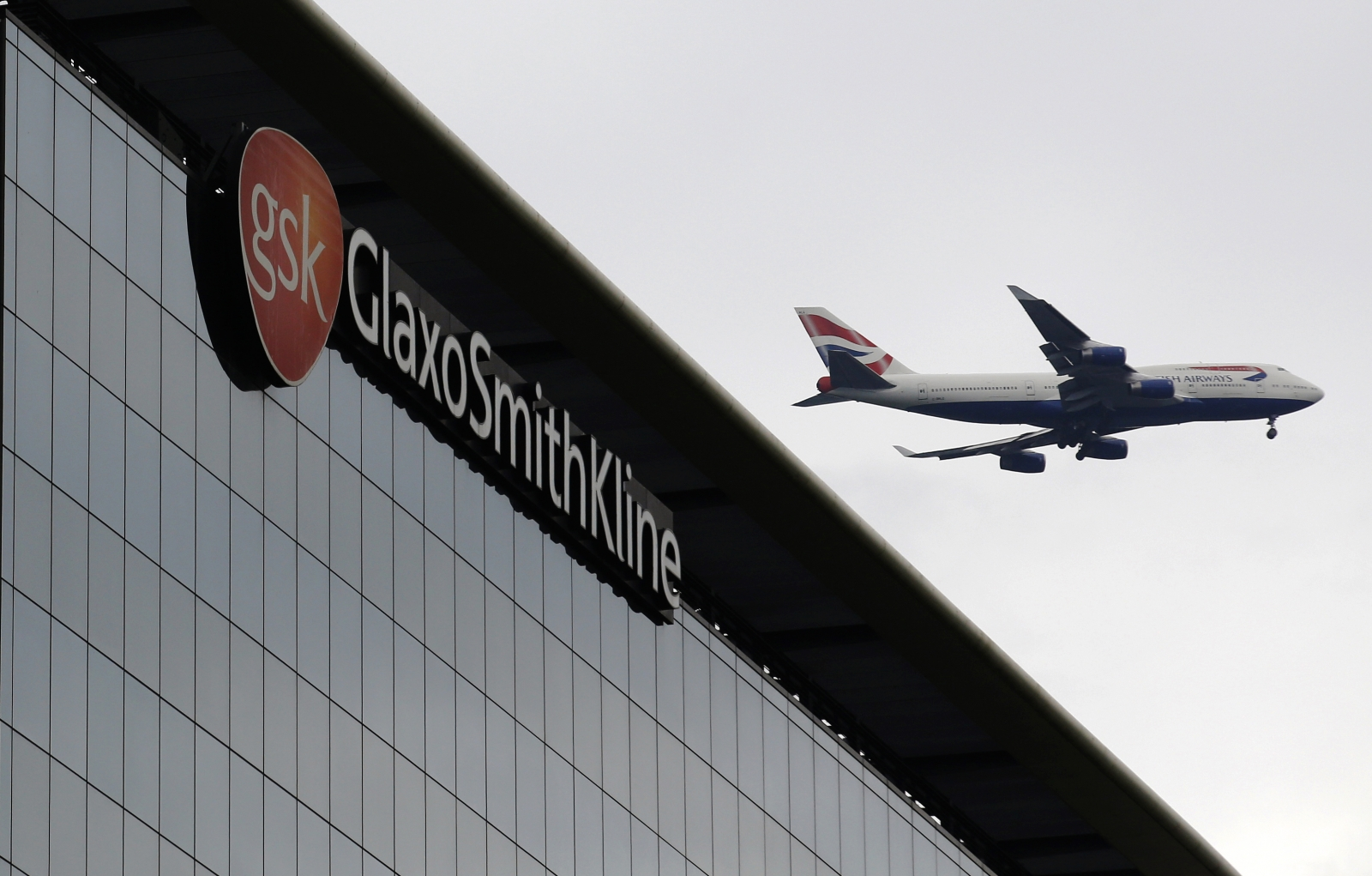A British Airways airplane flies past a signage for pharmaceutical giant GlaxoSmithKline (GSK) in London