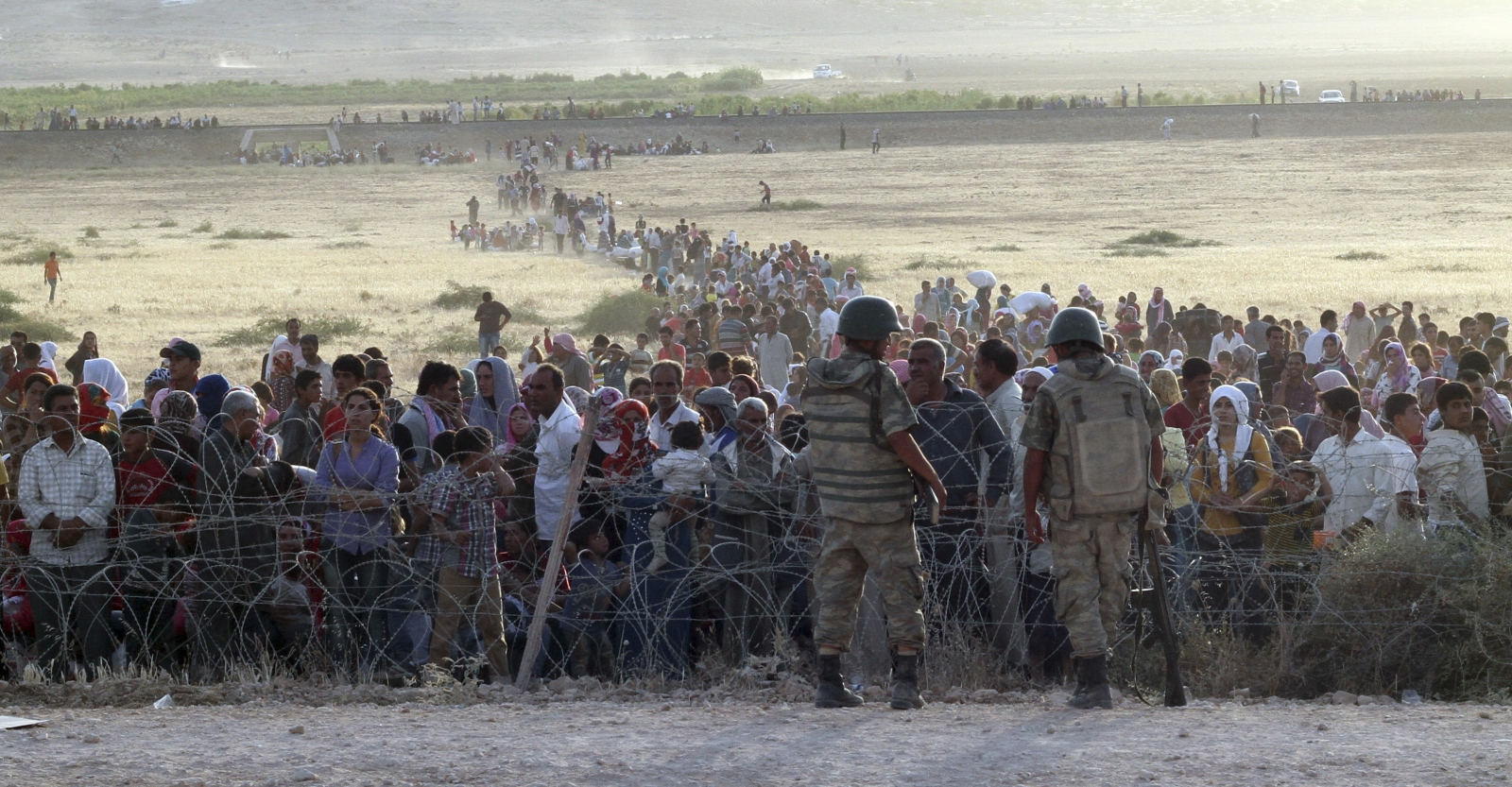 Turkish soldiers stand guard as Syrian refugees wait behind the border fences
