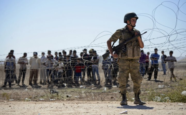 A Turkish soldier stands guard as Syrian Kurds wait behind the border fence near the southeastern town of Suruc in Sanliurfa province,