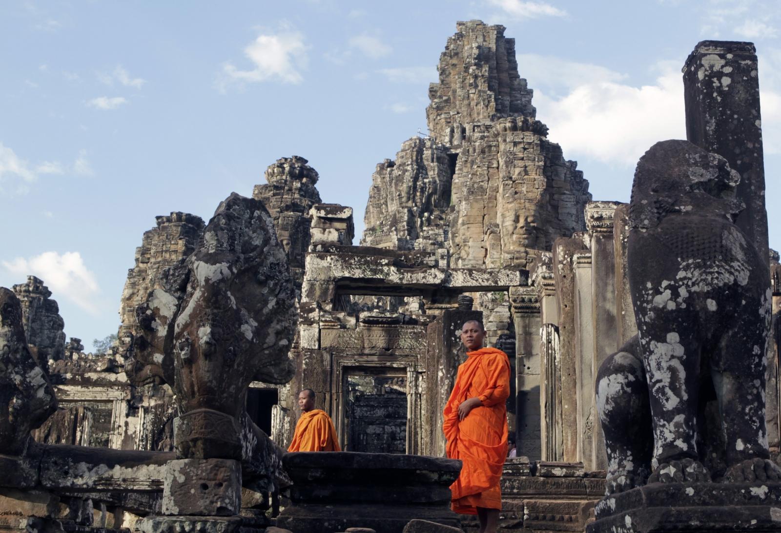 Monks walk around Bayon temple in Siem Reap