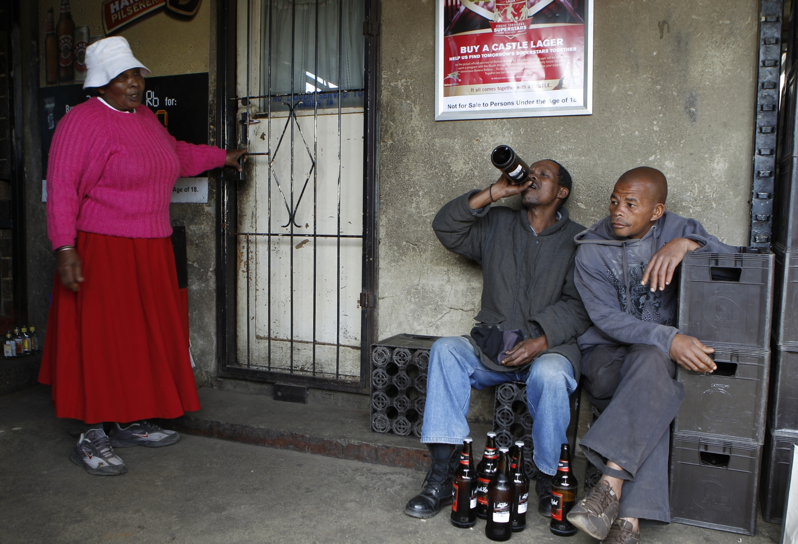A woman looks on as men drink beer at a sheeben (bar) in Soweto, southwest of Johannesburg August 8, 2012