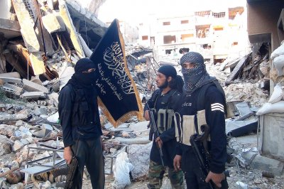 Fighters from the Nusra Front stand amid destroyed buildings in the south of Damascus, Syria