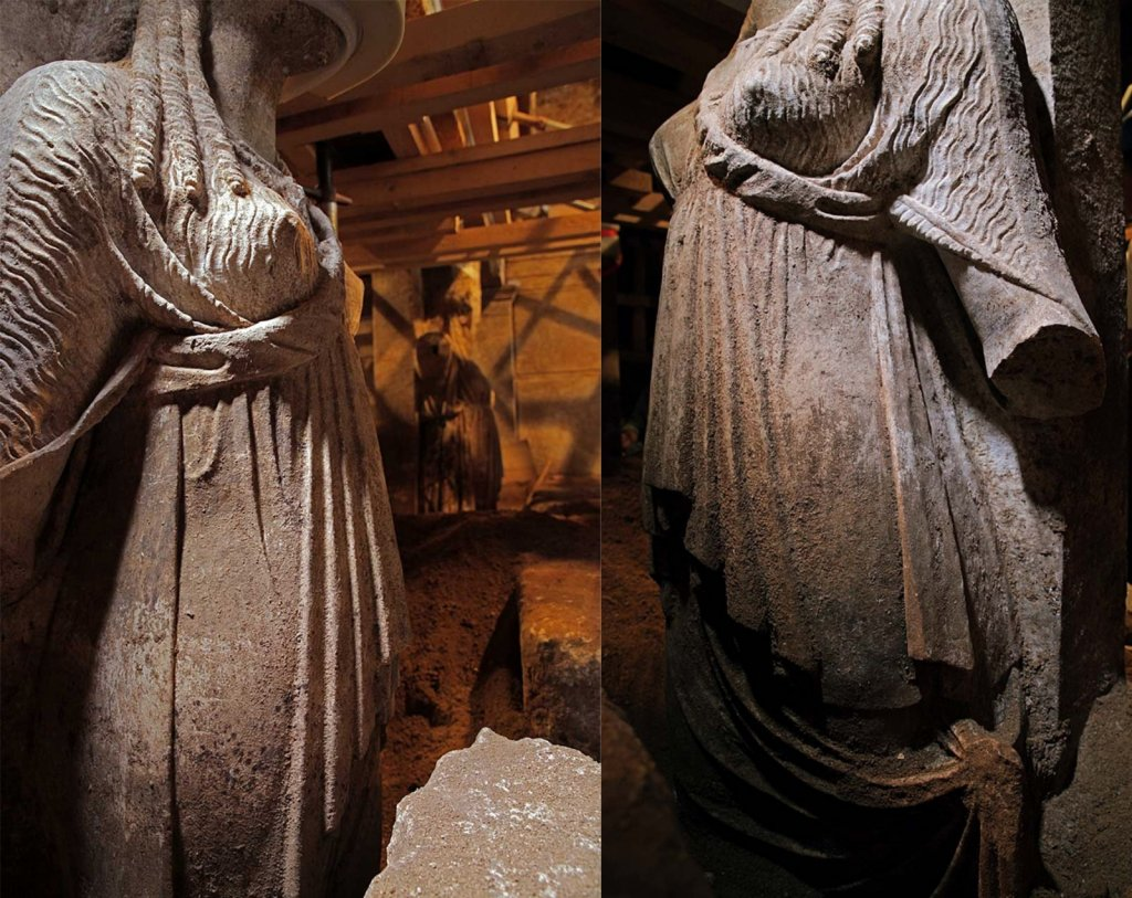 The caryatid statues being excavated from sandy soil in the Amphipolis tomb