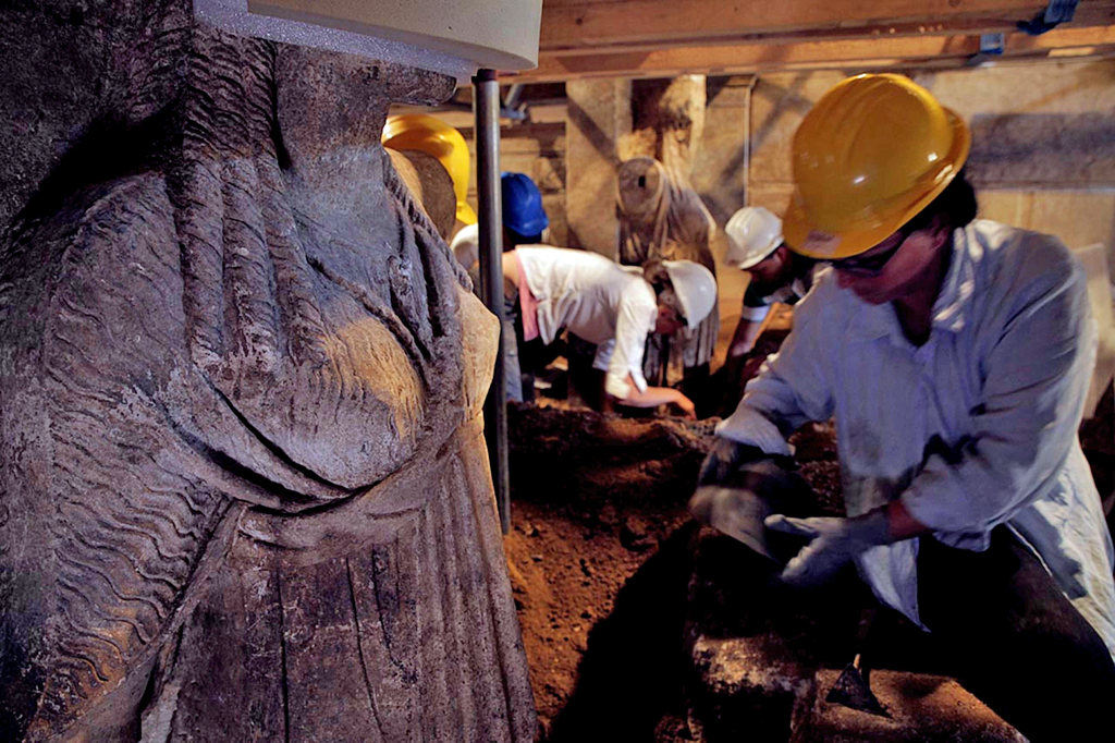 Excavating the caryatid statues from several feet of sandy soil