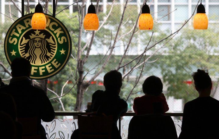 Customers sit inside a branch of Starbucks in the Jimbocho district of Tokyo