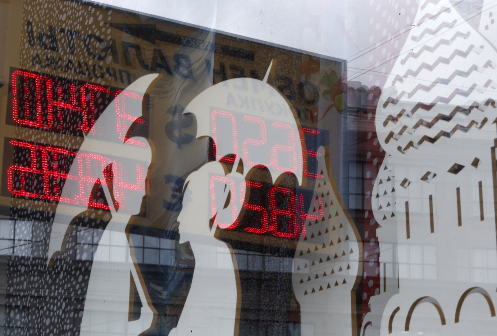 A board displaying currency exchange rates is reflected in a shop window in central Moscow