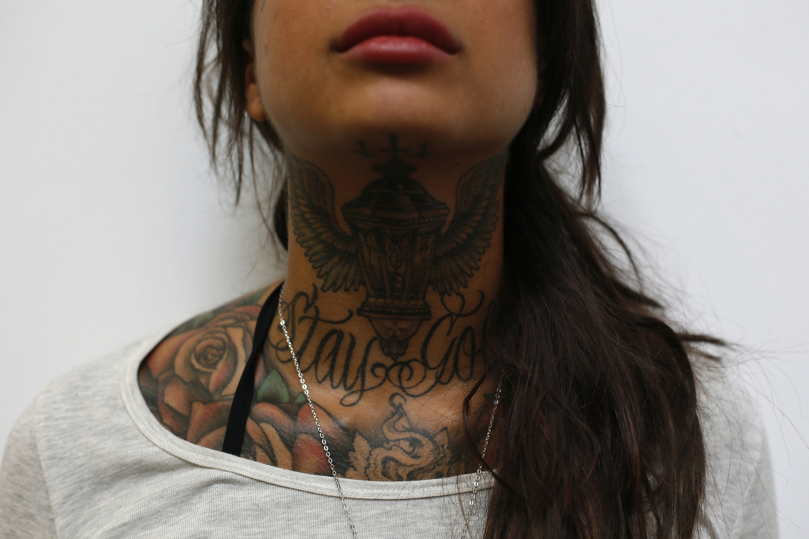 Cleo displays tattoos on her neck during the ninth London Tattoo Convention in London September 27, 2013