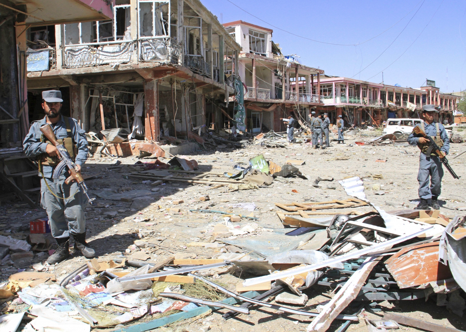 Afghan police stand guard among damaged buildings after a suicide attack in Ghazni Province
