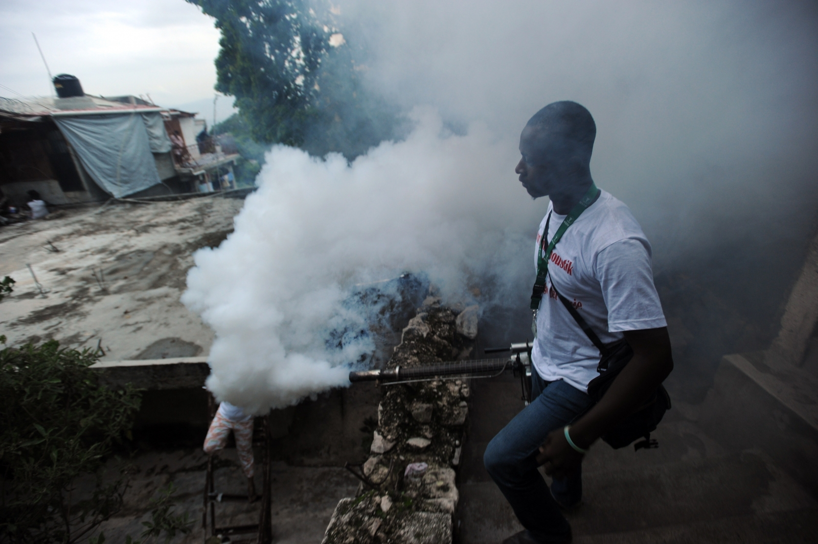 Health worker, Port-au-Prince, Haiti, fumigates for mosquitos