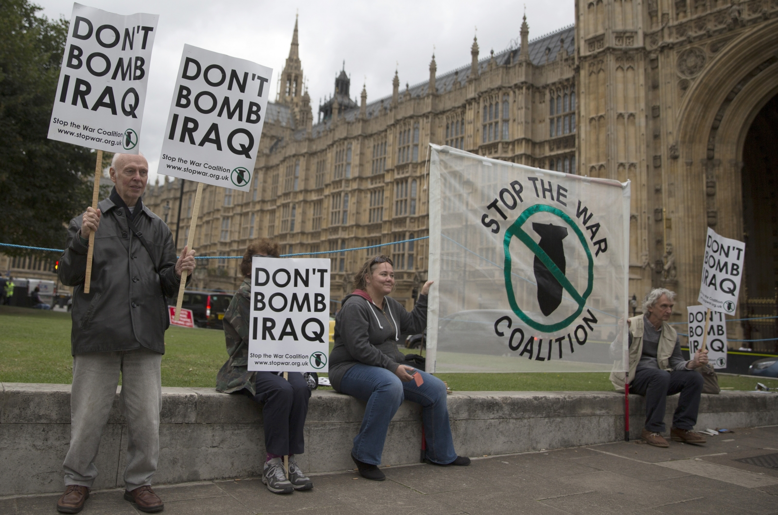 Demonstrators outside of the Houses Parliament protest against British military strikes in Iraq