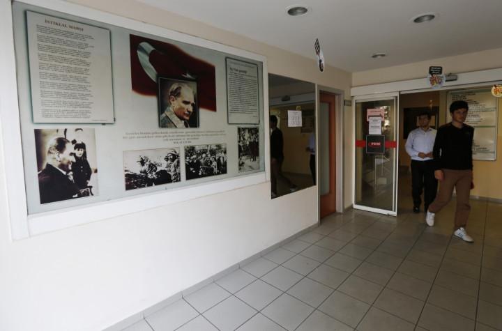 Students walk past photographs of modern Turkey's secular founder Mustafa Kemal Ataturk hanging on a wall at the entrance of FEM University Preparation School in Uskudar