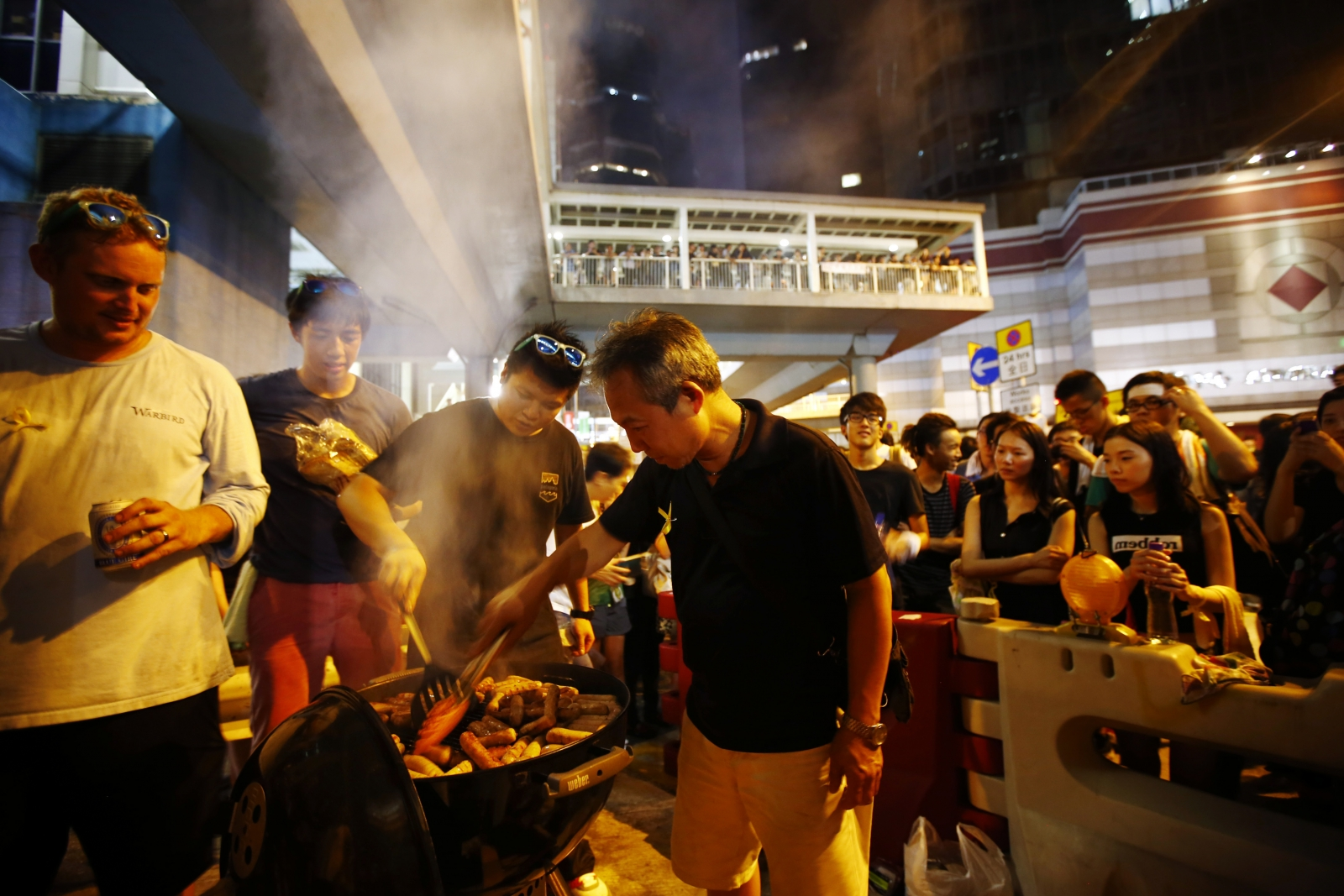 A man cooks sausages for protesters, who are blocking the main street to the financial Central district, outside the government headquarters in Hong Kong September 29, 2014