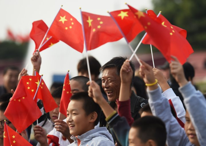 China National Day - People wave the national flag in Tiananmen Square at a memorial service to the nation's heros