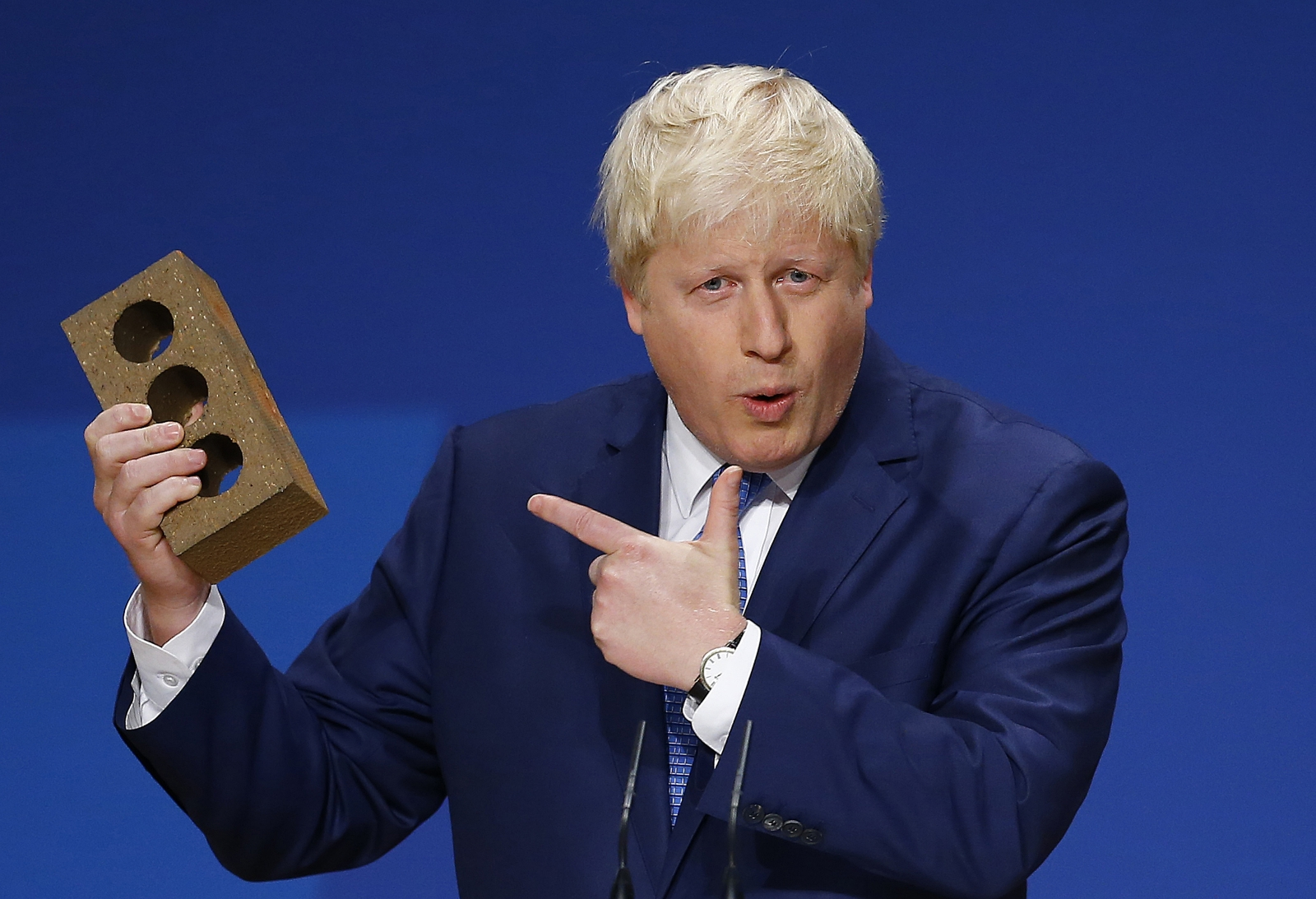 London Mayor Boris Johnson holds a brick as he speaks at the Conservative Party Conference in Birmingham, central England, September 30, 2014