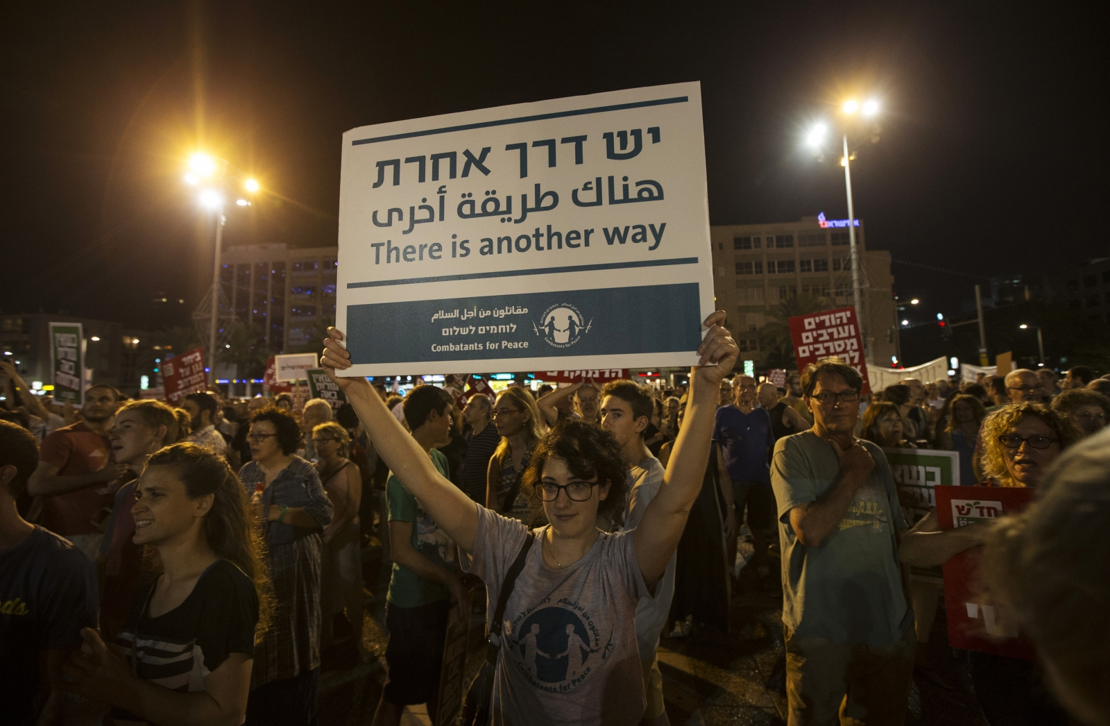 A woman holds up a placard during a peace rally in Tel Aviv's Rabin Square August 16, 2014.