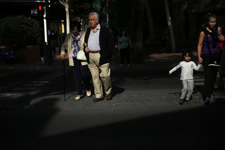 Pensioners cross the street in Madrid September 30, 2014.