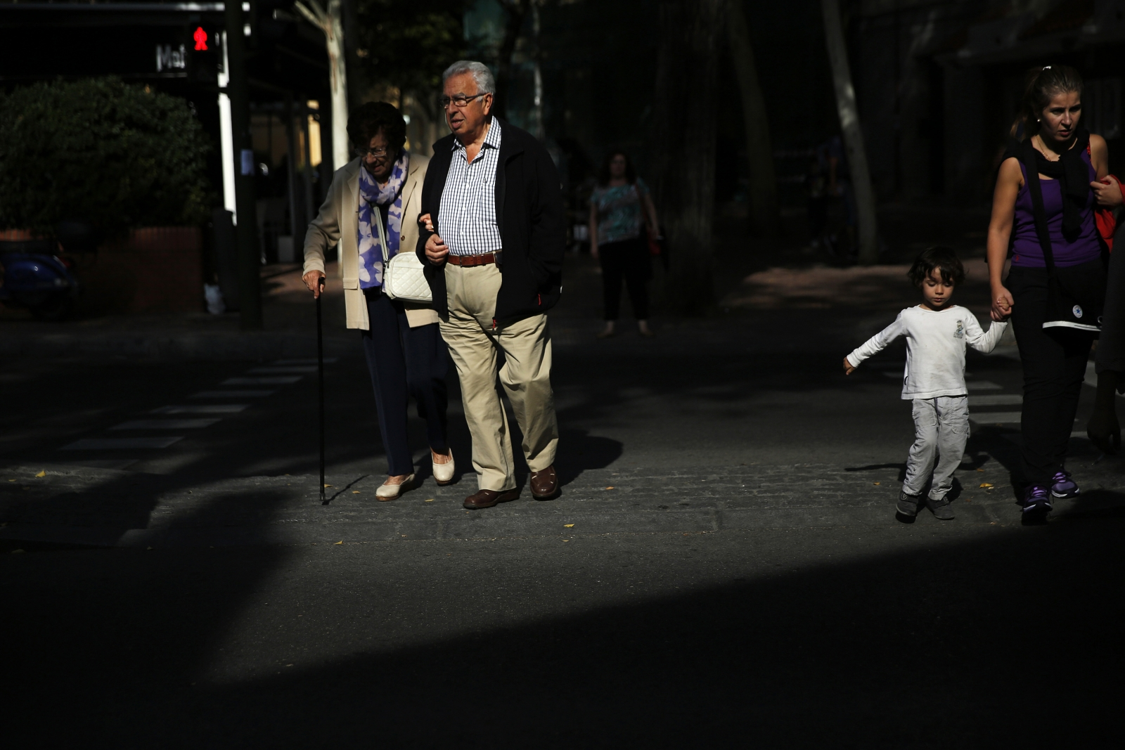 Pensioners cross the street in Madrid September 30, 2014.