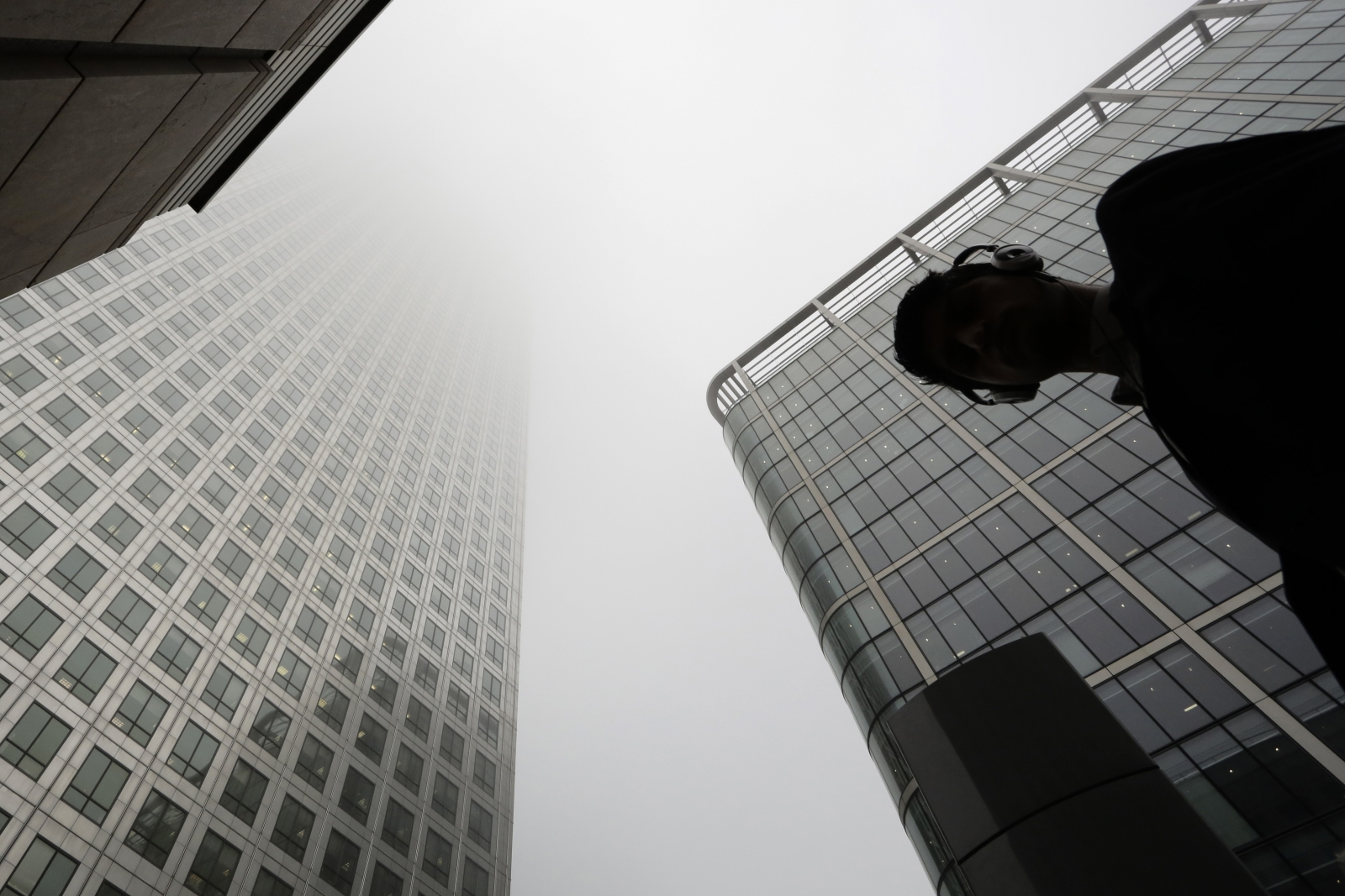 A man walks past a building in the morning mist at London's financial district of Canary Wharf September 16, 2014