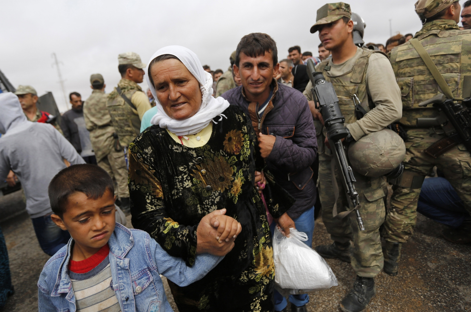 Syrian Kurds walk through Mursitpinar border crossing to return to their homes in the Syrian city of Kobani