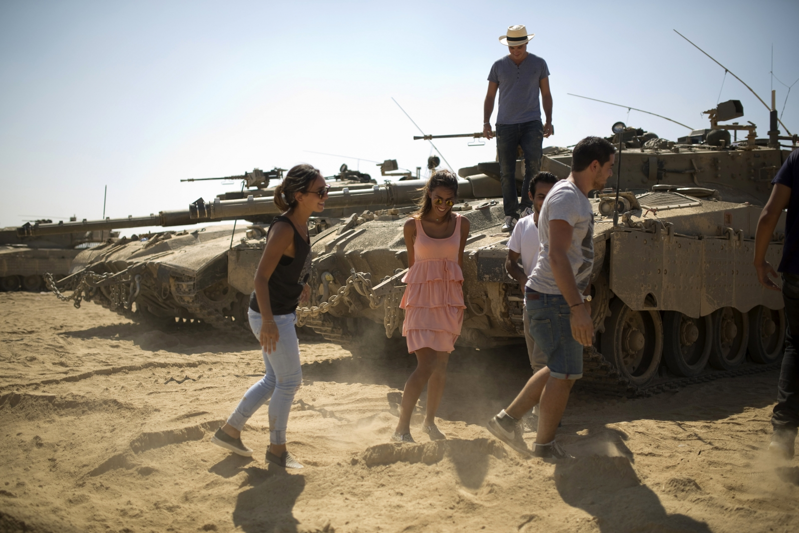 Tourists from Belgium and France walk near tanks at a staging area outside the northern Gaza Strip July 27, 2014.
