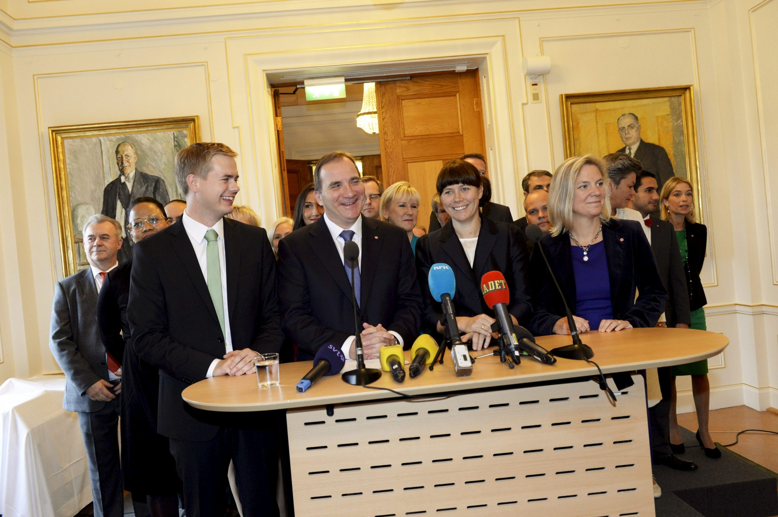 Swedish Prime Minister Stefan Lofven (front 2nd L) smiles as he stands with his new government during a news conference in Stockholm