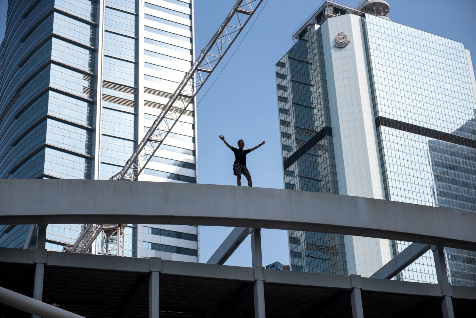 A man standing on top of a bridge overlooking a pro-democracy protest area threatens to jump