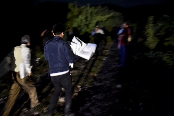 Officers bring body bags to the mass grave uncovered in Iguala last night. (AFP)