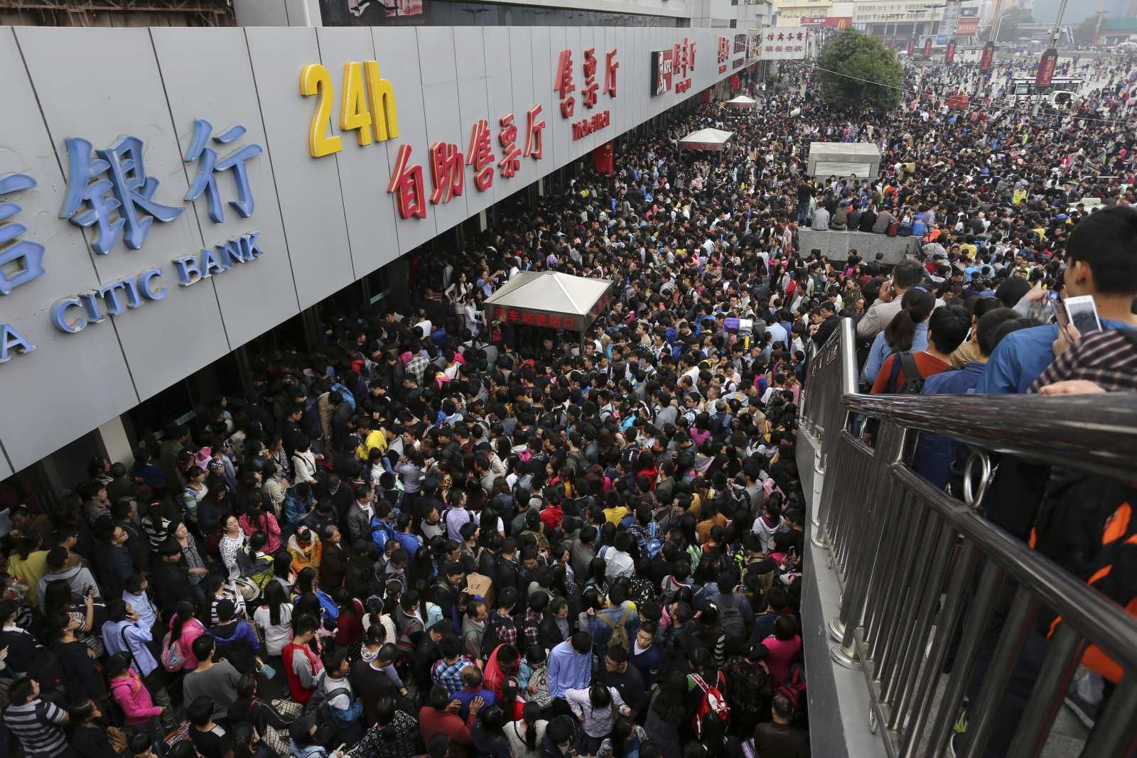 Passengers wait to get in the crowded Zhengzhou Railway Station, on the first day of the seven-day national day holiday, in Zhengzhou, Henan province October 1, 2014.
