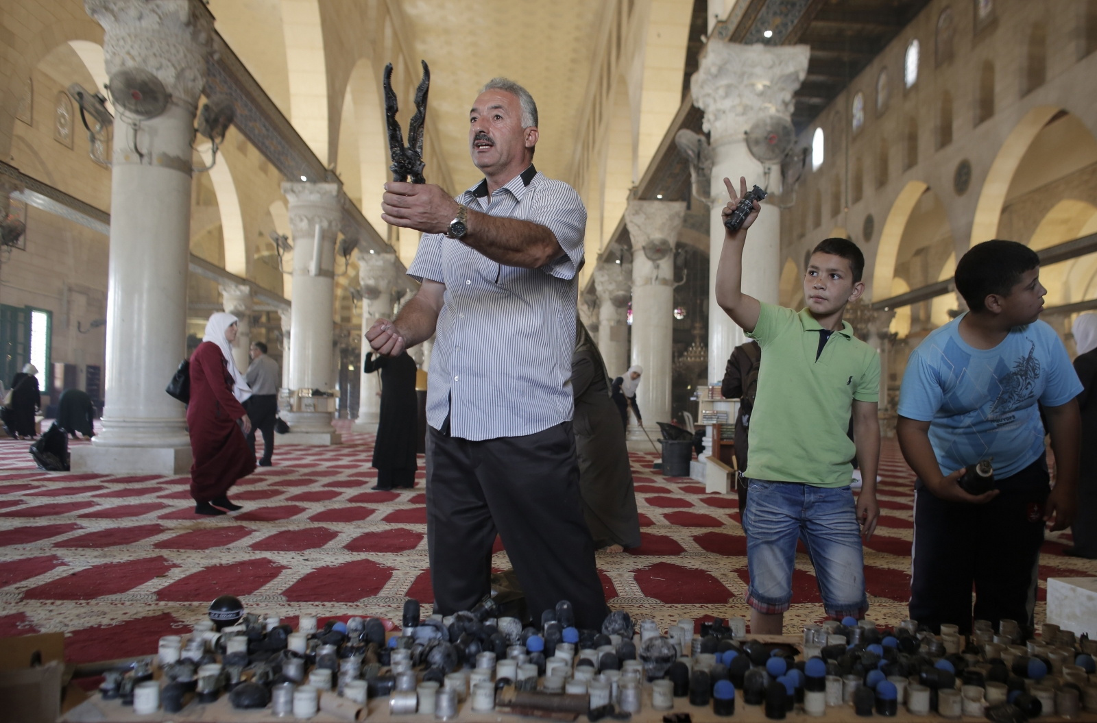 Palestinians display rubber bullets and stun grenades used by Israeli riot police inside the Al-Aqsa Mosque compound, Islam's third most holy site