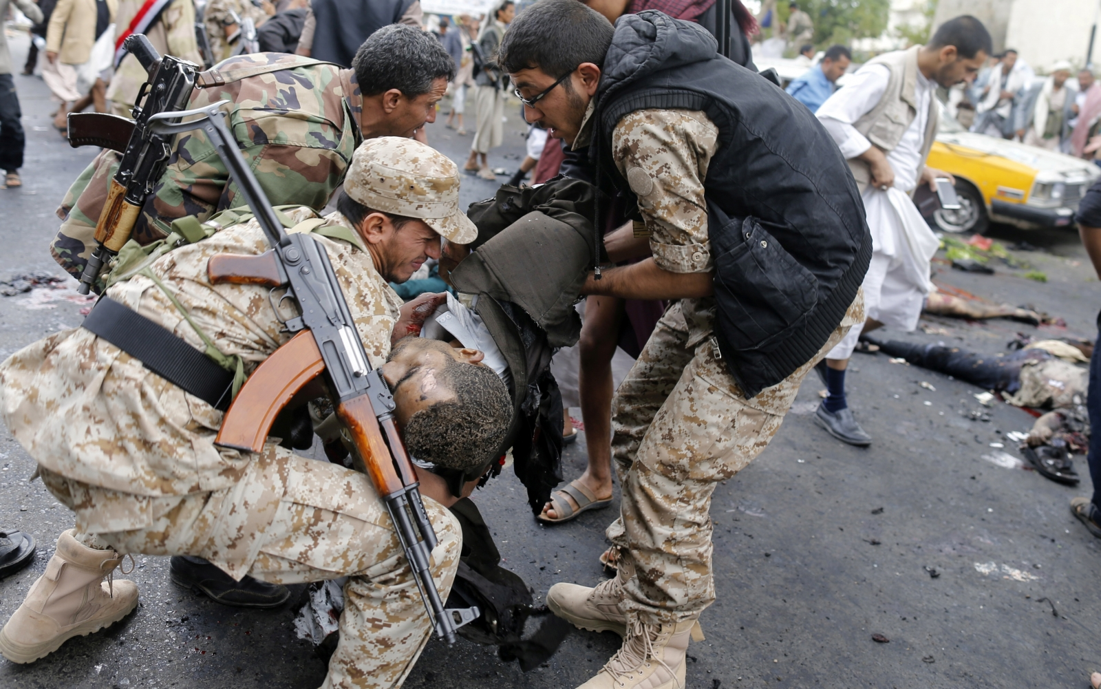 Shi'ite Houthi rebels carry a dead man at the scene of a suicide attack in Sanaa
