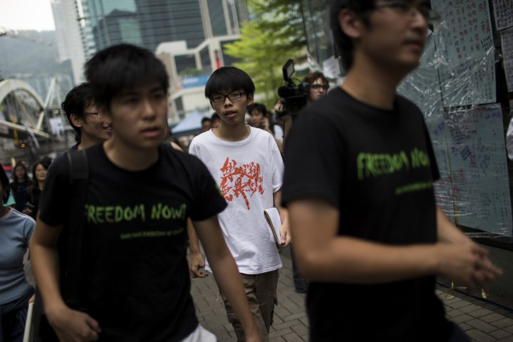 Joshua Wong (C), leader of the student movement,walks with Hong Kong Federation of Students's secretary-general Alex Chow (R) and vice secretary of the Hong Kong Federation of Students Lester Shum