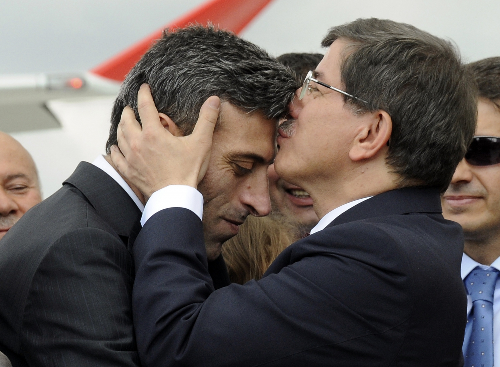 Turkish Prime Minister Ahmet Davutoglu (R) kisses Turkish Consul General of Mosul Ozturk Yilmaz on the forehead