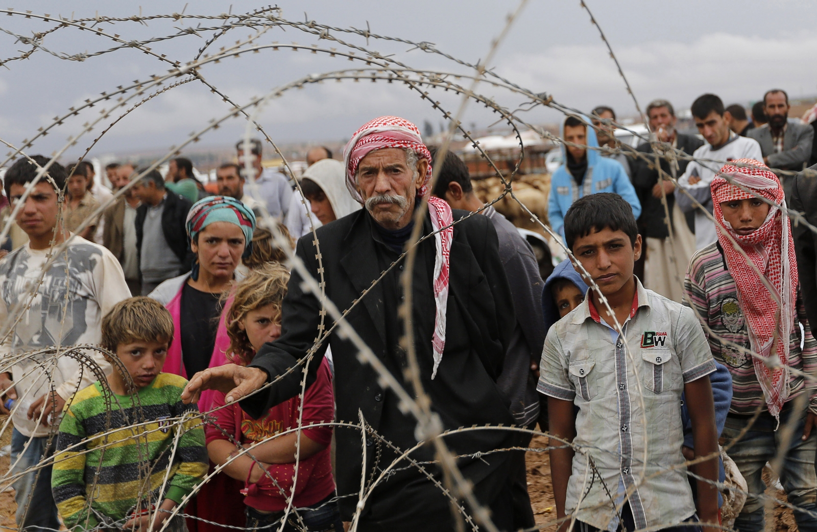 Syrian Kurds wait behind the border fences to cross into Turkey