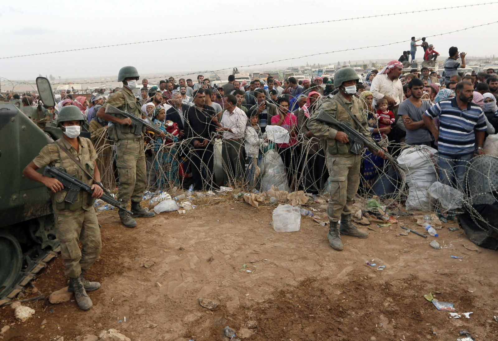 Turkish soldiers stand guard as Syrian Kurdish refugees wait behind the border fences