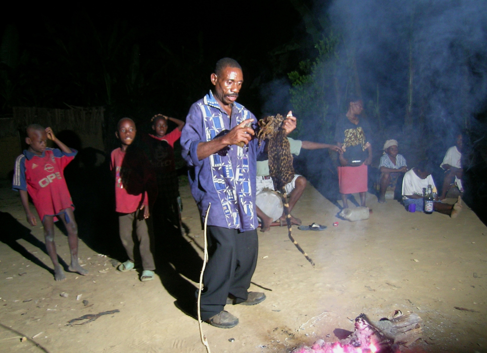 A African sorcerer performs a dance in front of a sacred fire