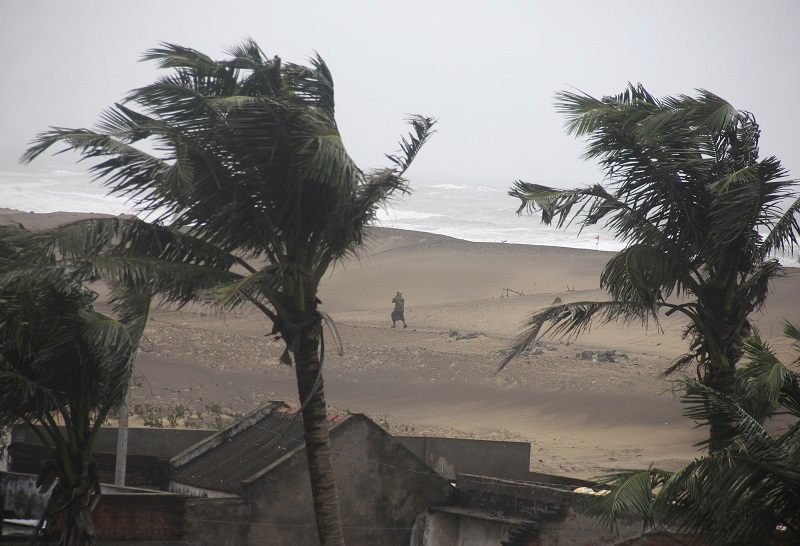 A man walks as strong winds blow along a beach in Gopalpur in the eastern Indian state of Odisha on 12 October 2014