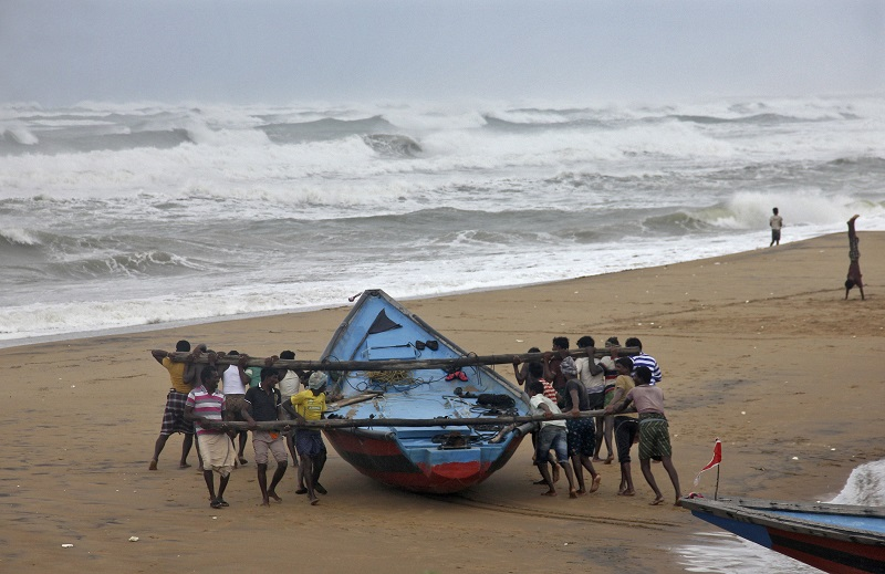 Fishermen move a fishing boat to a safer place along the shore as Cyclone Hudhud approaches