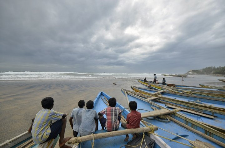 Children sit on fishing boats by the shore before being evacuated at Visakhapatnam district in the southern Indian state of Andhra Pradesh