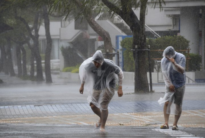 People struggle against strong wind and rain caused by Typhoon Vongfong on Japan's southern island of Okinawa